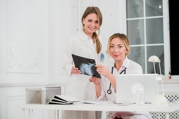 Dwa żeńskiego kobieta lekarza medycyny patrzeje promieniowanie rentgenowskie w szpitalu