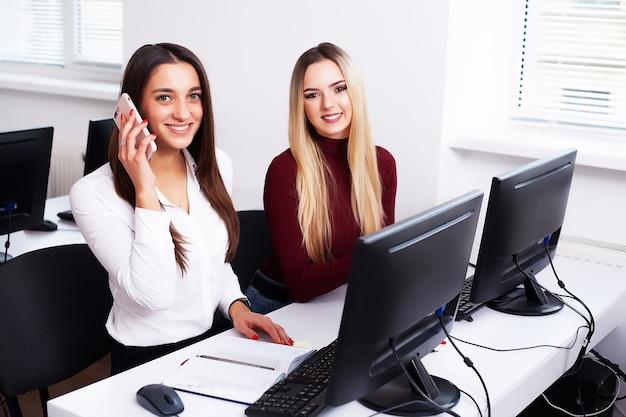 Dwa żeńskiego kolegi w biurze pracuje wpólnie.
