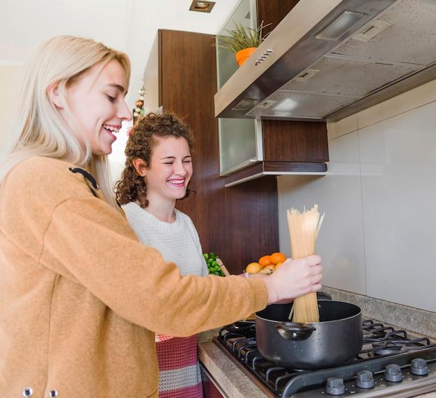 Dwa żeńskiego przyjaciela gotuje spaghetti w rondlu