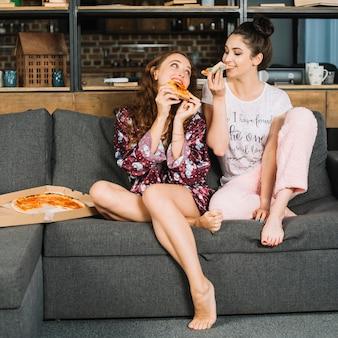 Dwa żeńskiego przyjaciela je pizzę w domu