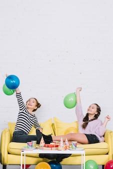 Dwa żeńskiego przyjaciela siedzi na kanapie cieszy się przyjęcia urodzinowego w domu