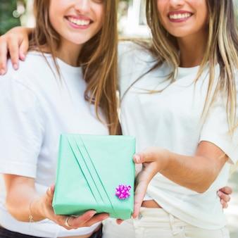 Dwa żeńskiego przyjaciela trzyma zielonego prezenta pudełko