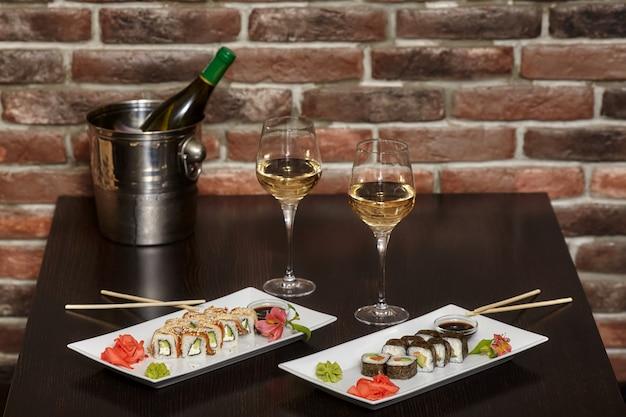 Dwa zestawy rolek sushi na białym talerzu z pałeczkami i kieliszkami do wina