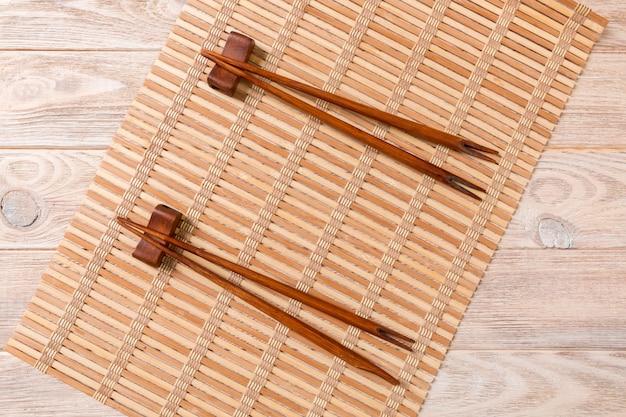 Dwa zestawy sushi pałeczki na drewnianym bambusie
