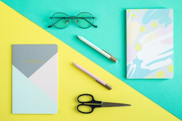 Dwa zeszyty, długopisy, nożyczki i okulary na niebieskim i żółtym tle