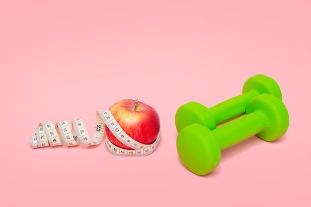 Dwa zielone hantle, czerwone jabłko i taśma miernicza na białym tle. zdrowy tryb życia. sprzęt sportowy. koncepcja fitness i diety. dobre odżywianie