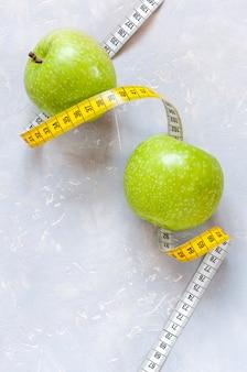 Dwa zielone jabłka i centymetr.