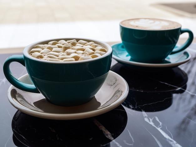 Dwa zielone kubki do kawy na stole