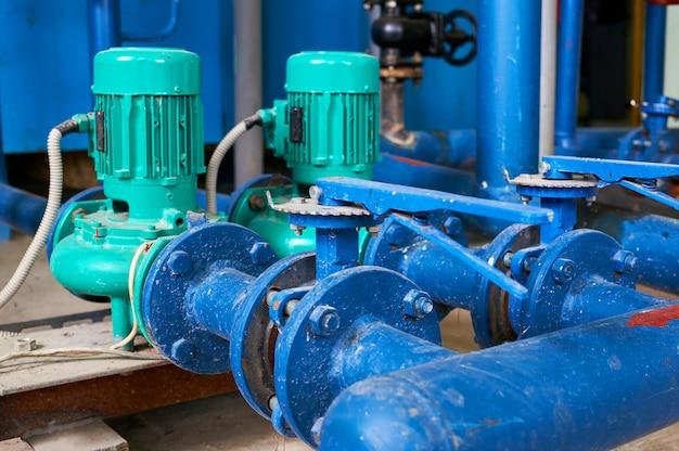 Dwa zielone przewody elektryczne pompy wody w kolorze niebieskim.