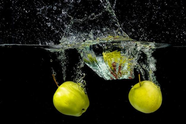 Dwa zielonego jabłczanego chełbotania w wodzie przeciw czarnemu tłu