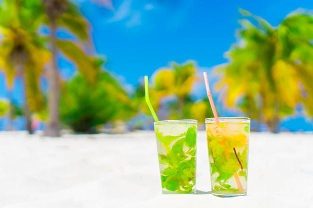 Dwa zimne smaczne koktajle mohito na białej, piaszczystej plaży w gaju palmowym