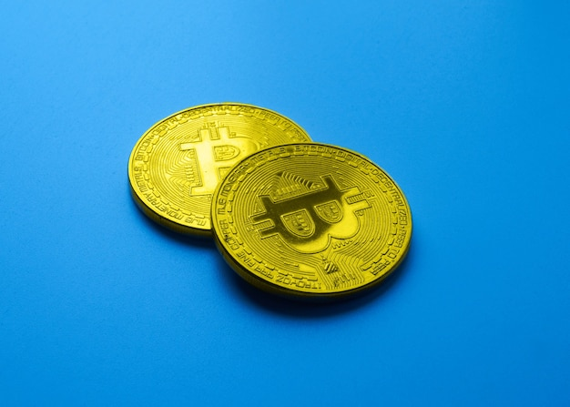 Dwa złote bitcoiny izolowane na niebieskim tle z bliska z miejscem na kopię, koncepcją wzrostu i upadku kryptowaluty