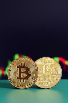 Dwa złote bitcoiny leżą na zielonej powierzchni na tle wyświetlacza, który przedstawia wzrost pozycji na wykresie