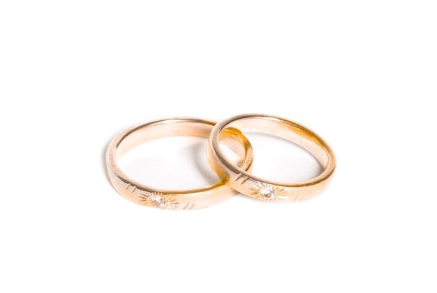 Dwa złote obrączki ślubne na białym tle, koncepcja tło obrączki ślubne
