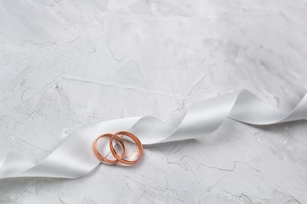 Dwa złote pierścienie i biała wstążka satynowa wesele wystrój lub koncepcja tło zaproszenie na ślub
