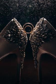Dwa złote pierścienie na białych butach ślubnych.