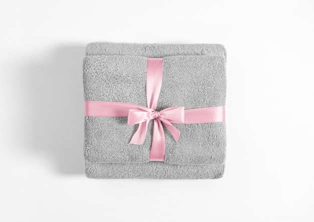 Dwa złożone ręczniki frotte związane różową wstążką na białym tle. stos szare ręczniki frotte na białym tle.