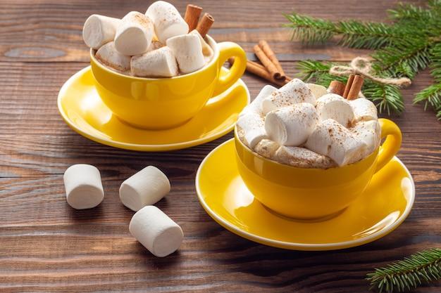 Dwa żółte ceramiczne kubki latte z piankami i cynamonem obok świerkowych gałęzi