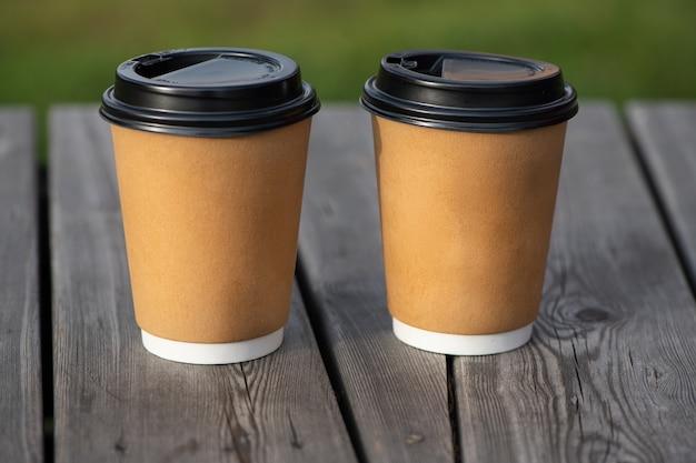 Dwa żółte papierowe filiżanki do kawy na drewnianej powierzchni do kawy i usług.