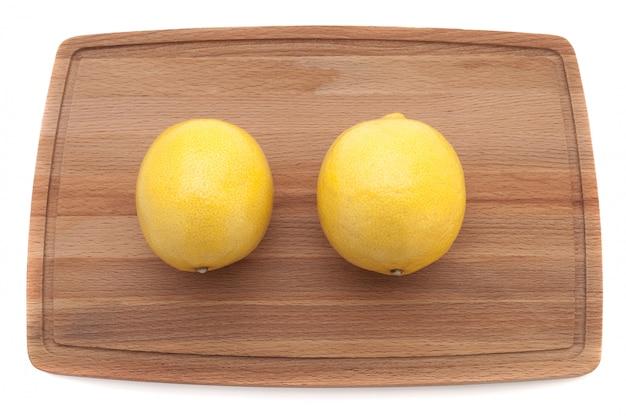 Dwa żółtej jaskrawej soczystej cytryny na drewnianej tnącej deski odgórnym widoku