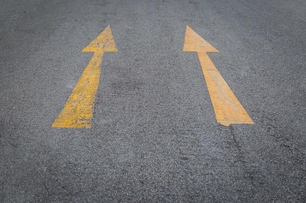 Dwa żółtych strzała starego i nowego directionon asfaltowej drogi tła