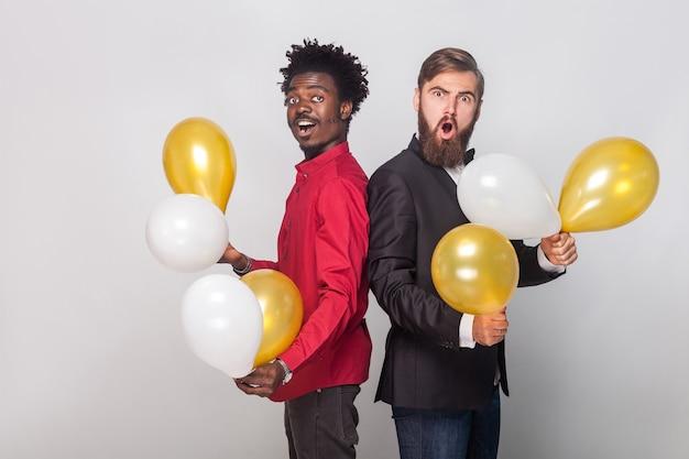 Dwa zszokowany przyjaciel ubrany w czerwoną koszulę i czarną kurtkę, trzymający wiele balonów i patrzący na kamerę z zszokowaną twarzą. strzał w pomieszczeniu