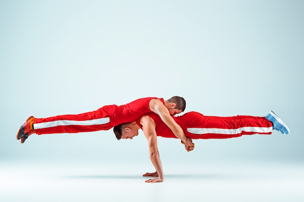 Dwaj akrobatyczni mężczyźni w równowadze stanowią