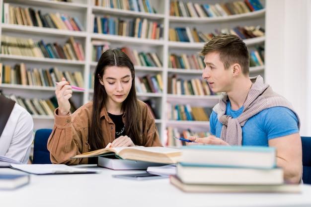 Dwaj atrakcyjni, uśmiechnięci, pewni siebie uczniowie, dziewczynka i chłopiec rasy kaukaskiej, siedzący przy stole i przygotowujący się razem do egzaminów w bibliotece przy użyciu różnych książek