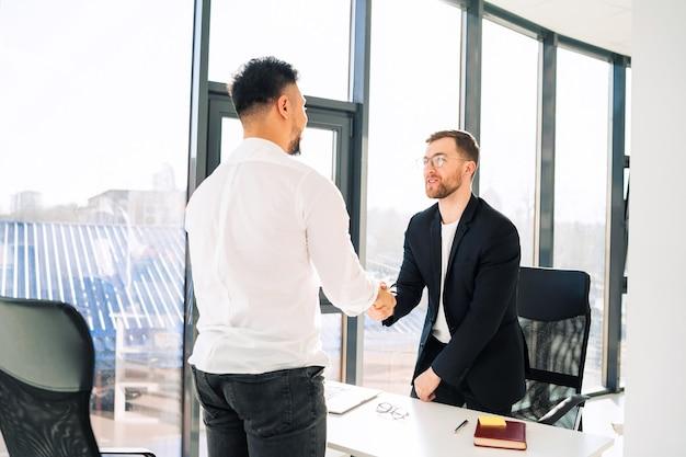 Dwaj biznesmeni podają sobie ręce w biurze