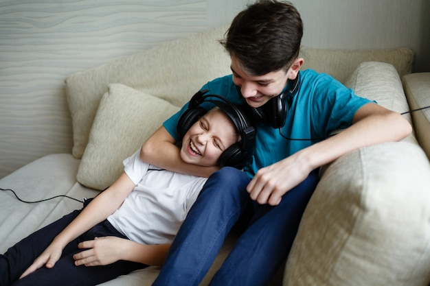 Dwaj bracia razem słuchają muzyki na słuchawkach w domu na kanapie