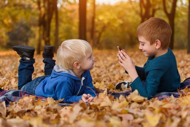 Dwaj bracia robią sobie zdjęcia, leżąc na żółtych jesiennych liściach. dzień upadku