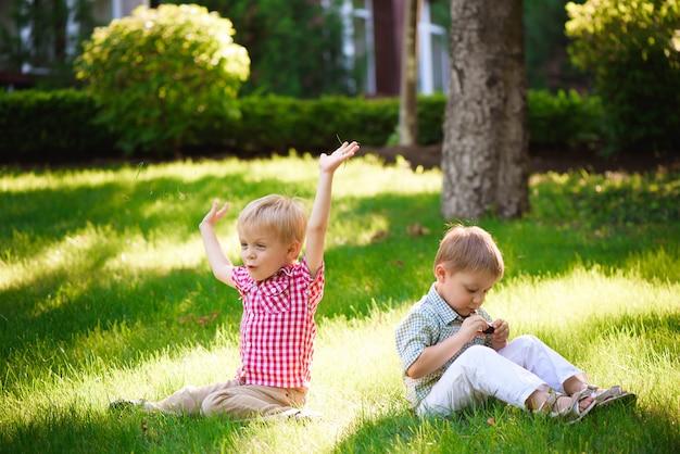 Dwaj bracia siedzą na słonecznej polanie w parku