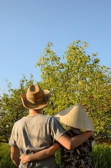 Dwaj bracia ubrani w różne narodowe kapelusze stoją plecami i przytulają się