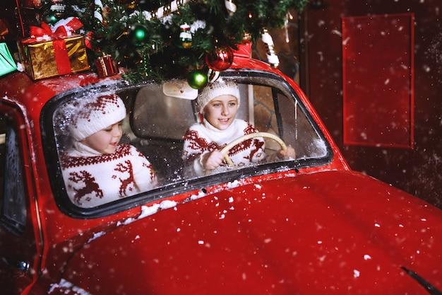 Dwaj bracia w swetrach z dzianiny z jeleniami siedzą w czerwonym noworocznym samochodzie i cieszą się nadejściem bożego narodzenia. dziecko zabawy na czas narodzenia. koncepcja święta x-mas.