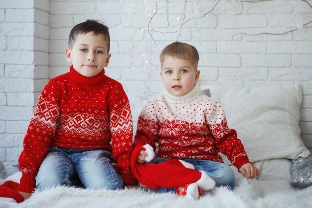 Dwaj bracia w świątecznym czerwonym swetrze z wizerunkiem jelenia siedzącego na łóżku w pobliżu poduszek.