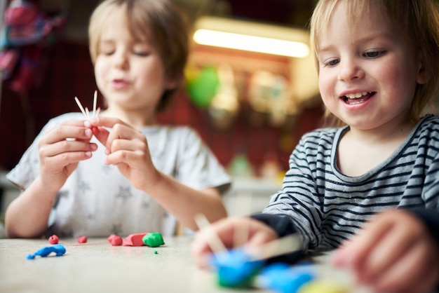 Dwaj bracia wykonują trójwymiarowe figurki z plasteliny i patyków