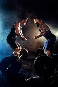 Dwaj brodaci wytatuowani muskularni mężczyźni patrzą na siebie i krzyczą na siłowni
