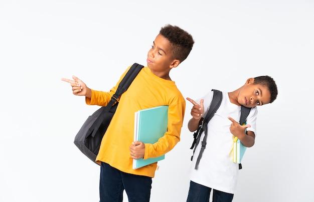 Dwaj chłopcy afroamerykanie nad izolowanym białym i wskazujący na bok