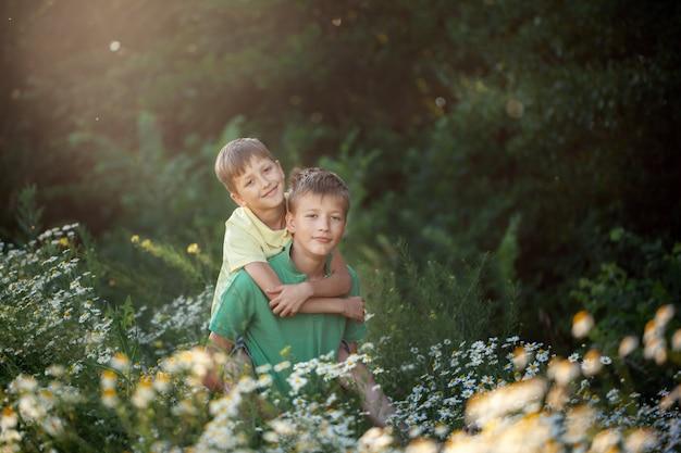 Dwaj chłopcy bracia przyjaciele przytulanie w słoneczny letni dzień. pojęcie przyjaźni.