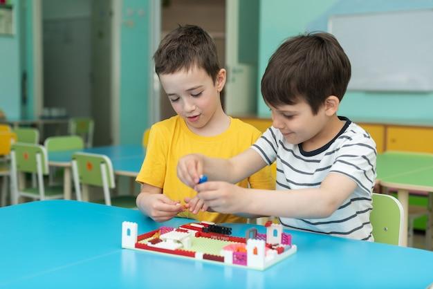 Dwaj chłopcy entuzjastycznie grają w lego w przedszkolu w czasie wolnym w przedszkolu