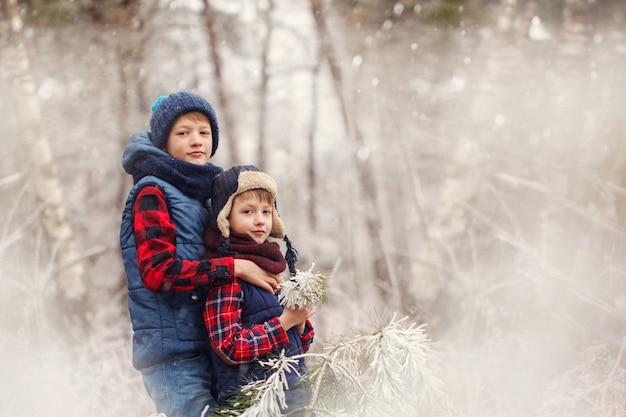 Dwaj chłopcy przyjaciele przytulanie w zimowym lesie. braterska miłość. pojęcie przyjaźni