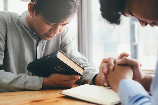 Dwaj chrześcijanie modlą się razem nad świętą biblią.