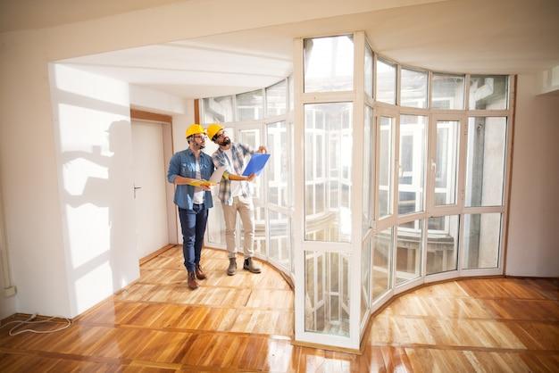 Dwaj czarujący młodzi architekci z żółtymi czapkami bezpieczeństwa sprawdzają postępy w swoich projektach, porównując wnętrze z planami w pobliżu okna w bardzo dużym budynku.