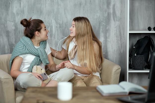 Dwaj emocjonalnie szczęśliwi przyjaciele dzielą się muzyką online przez słuchawki.