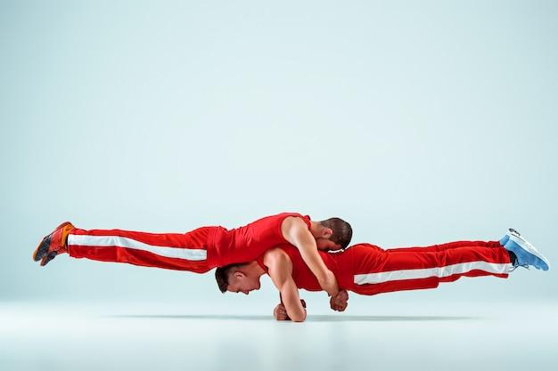Dwaj gimnastyczni akrobatyczni kaukascy mężczyźni w równowadze stanowią