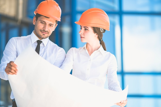 Dwaj inżynierowie spoglądają na plan projektu na tle budynku
