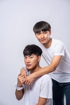 Dwaj kochający się mężczyźni przytulają się od tyłu.