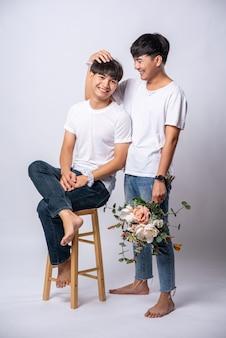 Dwaj kochający się mężczyźni trzymali się za głowy i usiedli na krześle.
