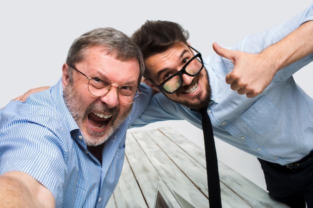 Dwaj koledzy biorący im zdjęcie siedzą w biurze