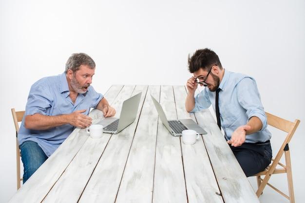 Dwaj koledzy pracujący razem w biurze na białej ścianie